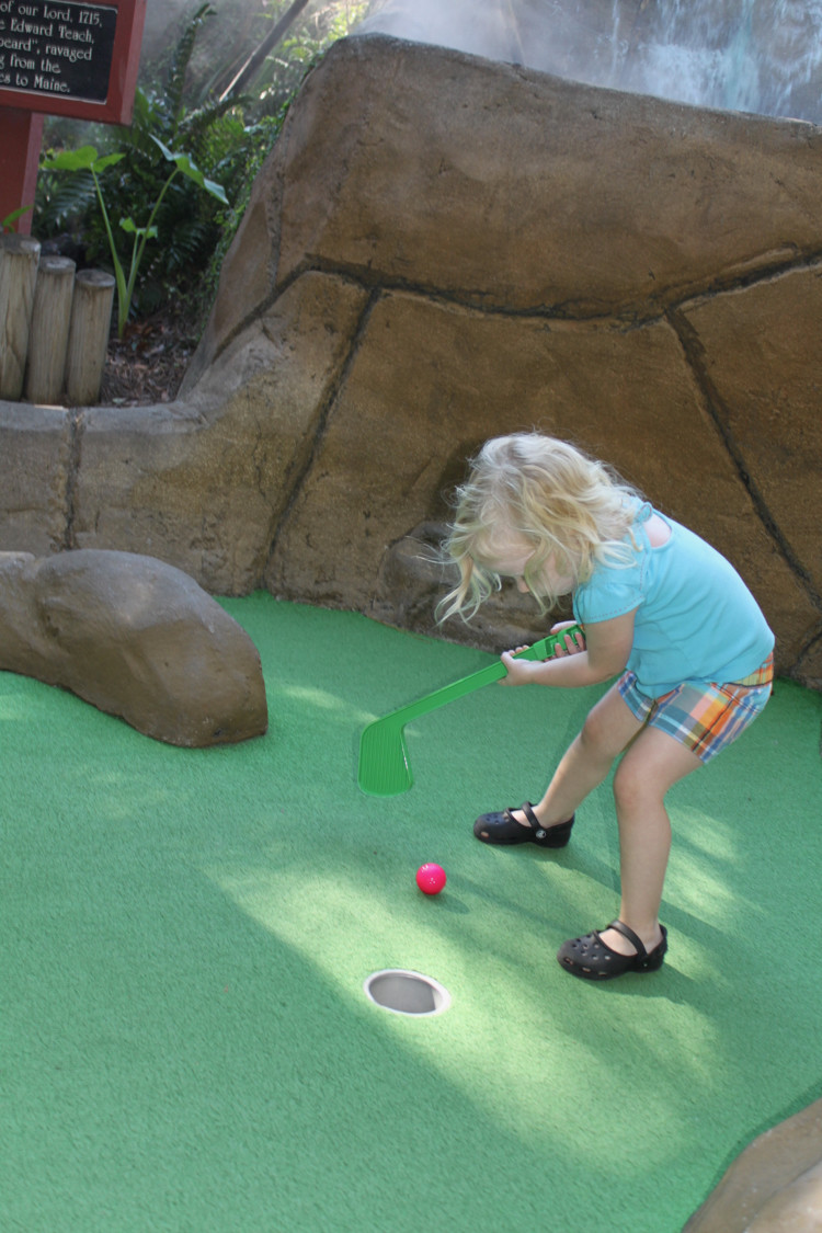 preschooler plays mini golf with a backwards club