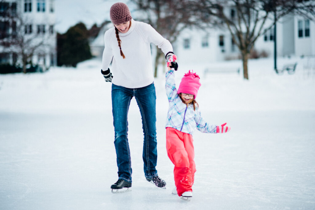 Parent and child ice skating during Schnee Days in Elkhart Lake Wisconsin.