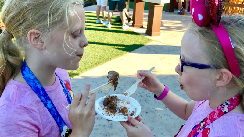 two young girls enjoy a sample of kid-friendly food at the Epcot International Food and Wine Festival