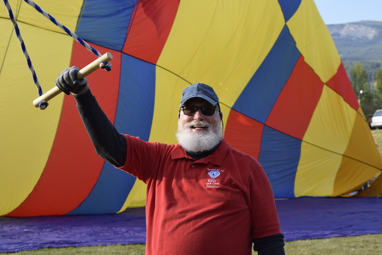 Travel bucket list experience -- volunteering as part of the hot air balloon crew like a bearded man holding a balloon at the Snowmass Balloon Festival in Colorado.