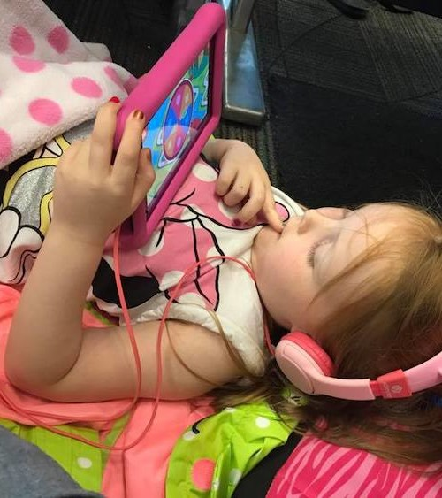 School-age kid lying down with an Amazon fire tablet and kid-friendly headphones - two of our favorite travel accessories for kids