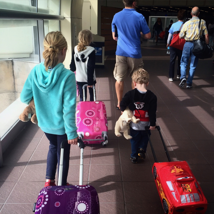 Three school-age kids pull carryon luggage behind them through an airport