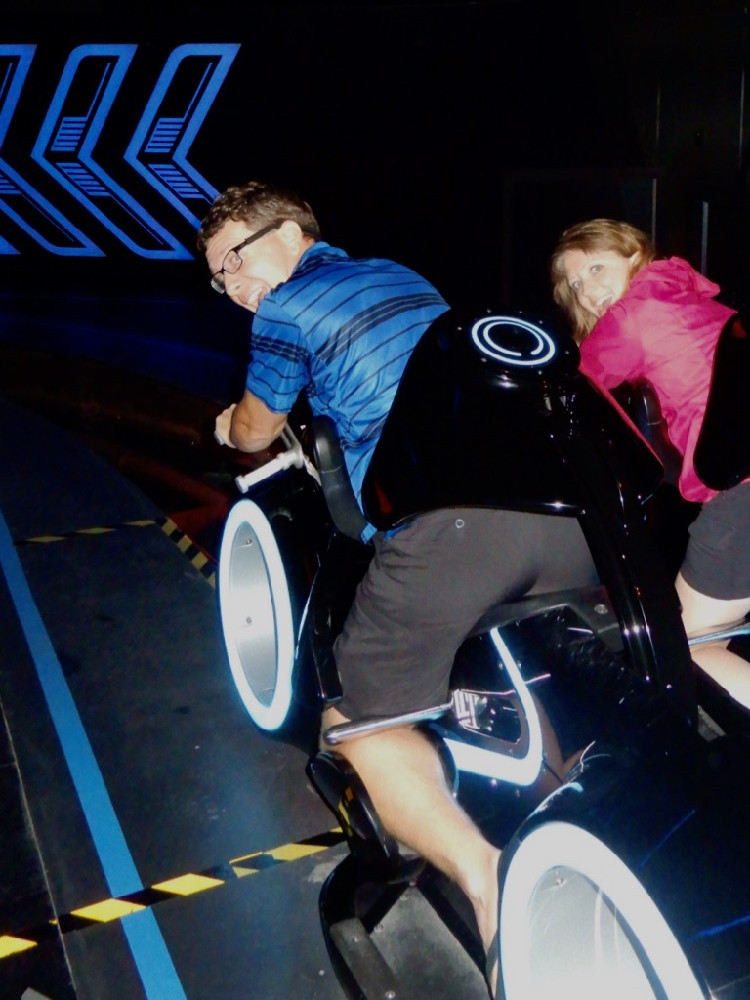 a man and woman sit on the Tron Lightcycle Power Run ride vehicles in Shanghai Disneyland park