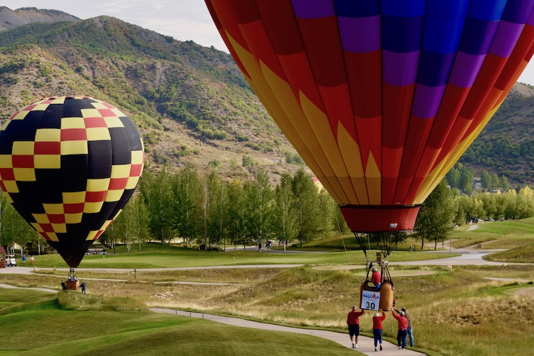 Travel bucket list experience -- walking hot air balloons back to the launch field at the Snowmass Balloon Festival in Colorado.
