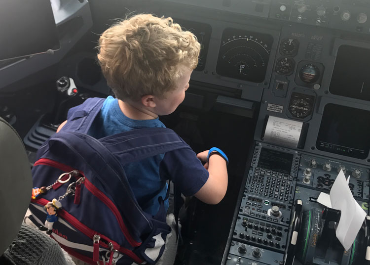 A young boy sitting in an airplane cockpit talking to a pilot, wearing a kid-friendly backpack as a carryon