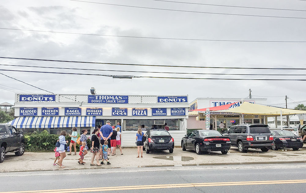People still line up in the rain to get donuts from Thomas' Donut Shop in Panama City Beach, FL.