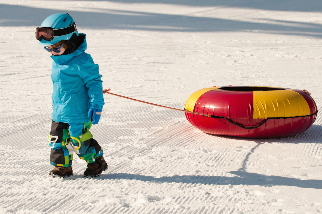 Tips for snow tubing with kids during a winter family vacation include finding a park with a magic carpet so little ones don't get tired dragging their tube up a hill.