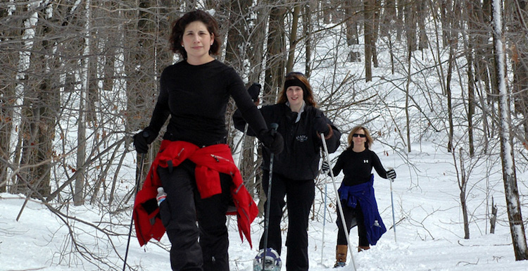 Girls ski trip can mean downhill skiing or cross country skiing on a winter girlfriend getaway - three women in woods at Seven Springs, one of many PA ski resorts #SkiPA