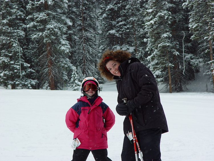 Tips for snow tubing with kids include wearing goggles and the right outerwear like a little girls and her mom.