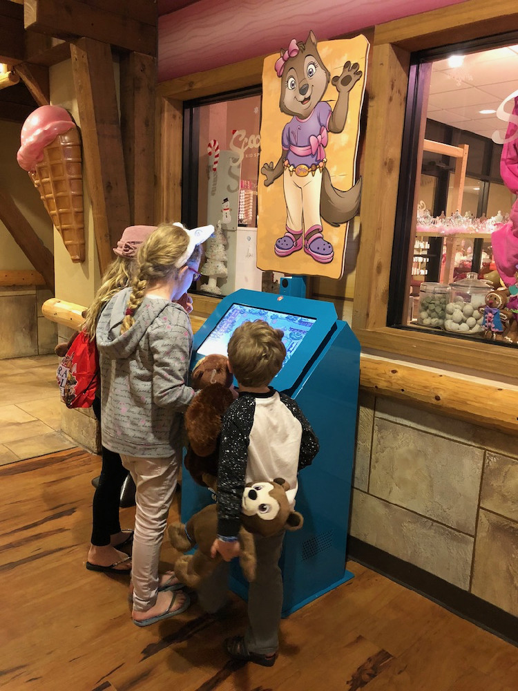 Three children stand at the Clubhouse Crew kiosk at Great Wolf Lodge, holding plush animals from the Creation Station in the hotel