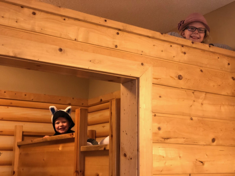 Kids peek over a bunk bed with a ladder in a KidCabin suite at Great Wolf Lodge