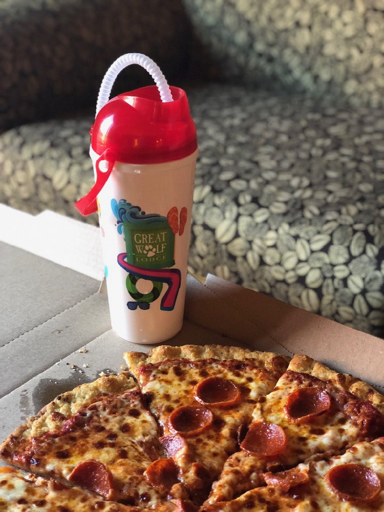 pizza in the foreground, from Hungry as a Wolf at Great Wolf Lodge; a refillable mug for soda and Icees in the background - TravelingMom