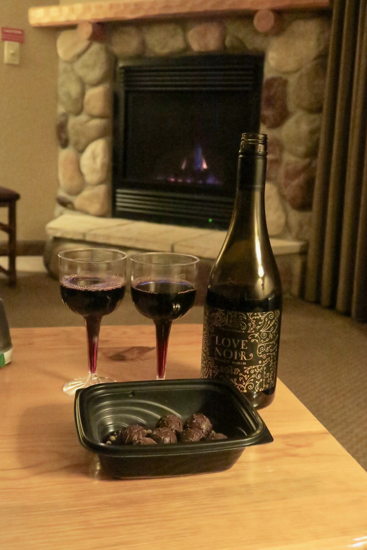 A bottle of wine, two plastic wine glasses, and chocolate truffles, part of the Wine Down Service at Great Wolf Lodge in Mason, Ohio