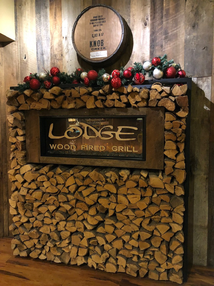 A stack of wood serving as a sign for the Lodge Wood Fired Grill at Great Wolf Lodge.