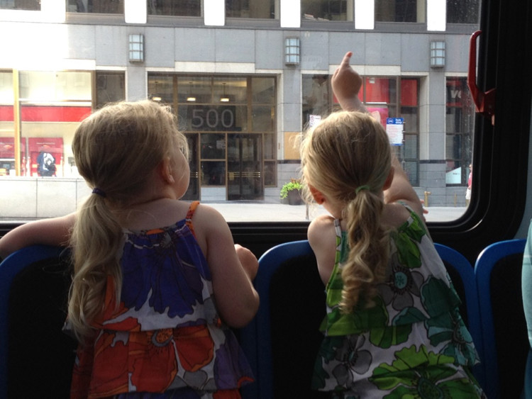 Two preschool girls look out the window on a Chicago bus during an off the beaten path spring break trip.