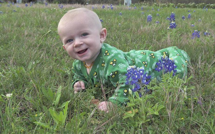 baby boy in green onesie laying in bluebonnet field texas
