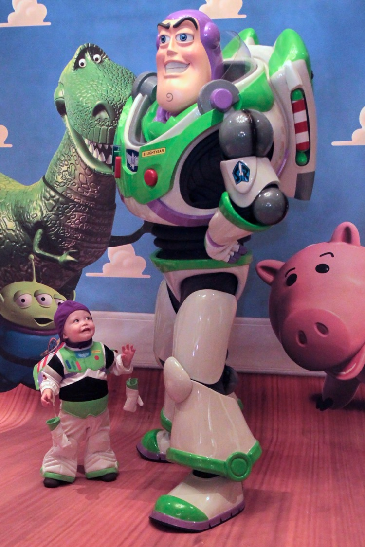 A toddler boy dressed as Buzz Lightyear meets his hero, full-size Buzz, a character encounter at Disney Toy Story Land opening in June 2018