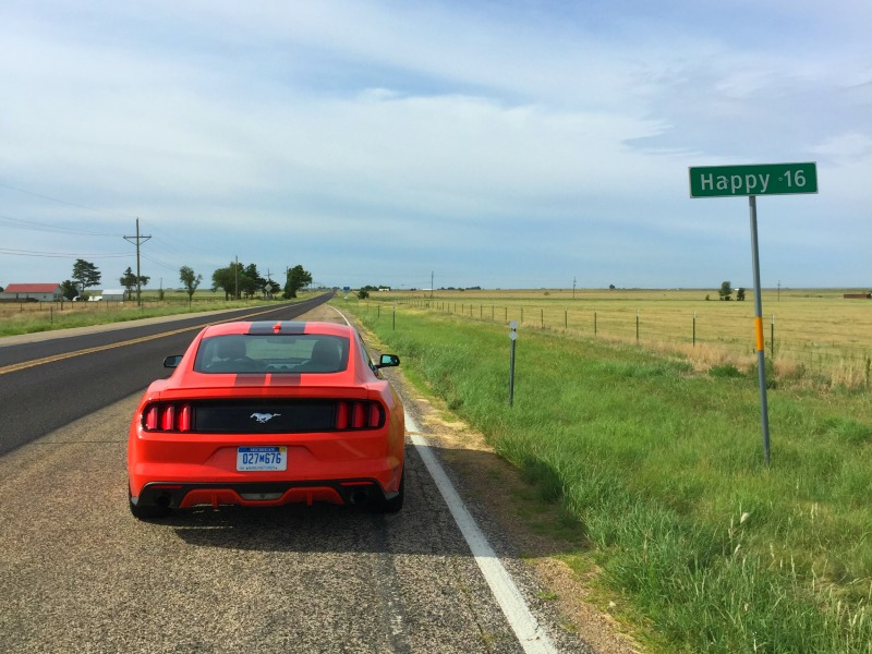 Happy Texas sign with red Ford Mustang in the photo on a Texas Road trip