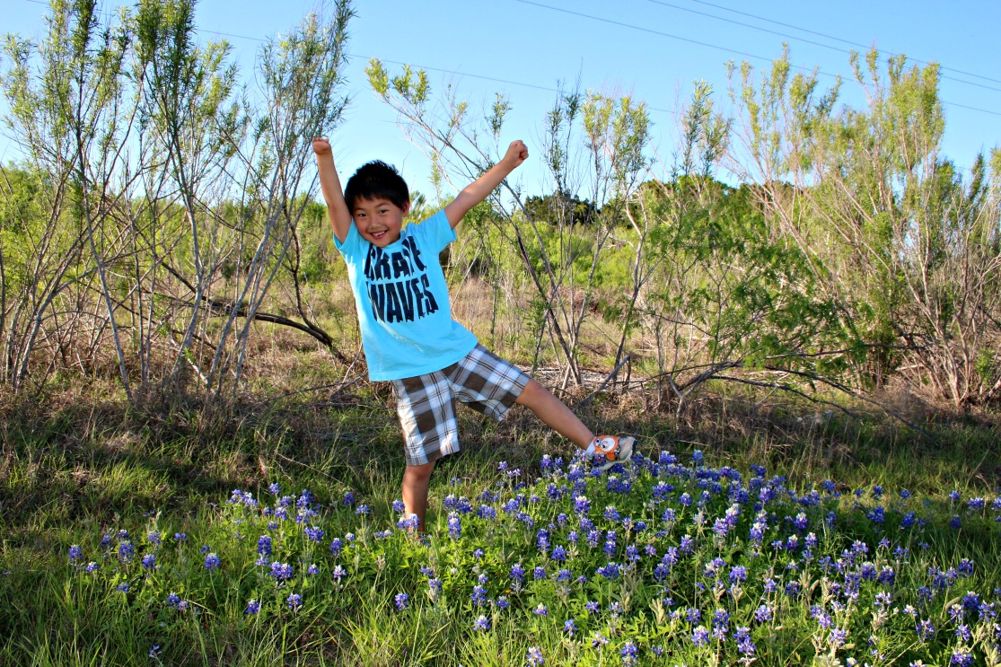 young boy jumping a field of Texas bluebonnets