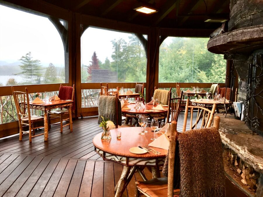 Adirondack style dining tables on an outside deck at the Lake Placid Lodge, one of the best restaurants in Lake Placid NY