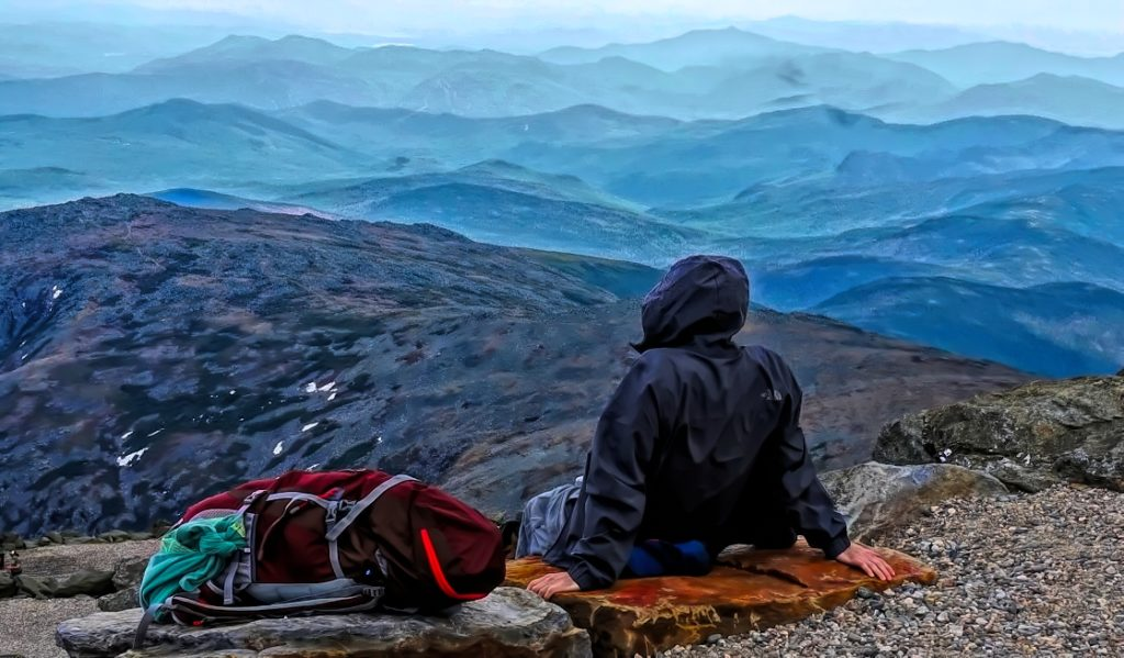 A hiker rests at the top of Mount Washington