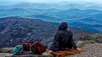 A hiker rests at the top of Mount Washington - TravelingMom