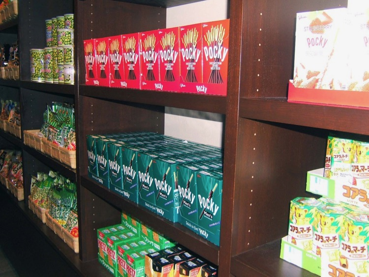 a shelf of pocky and other candy at the Japan pavilion in Epcot; candy from each country is one of our favorite disney world snacks!