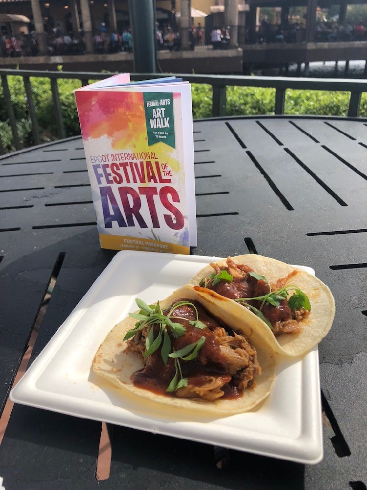 tacos and a festival of the arts booklet, from Epcot; an example of food items available at outdoor kitchens, and some of the best Epcot snacks