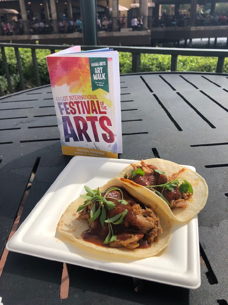 tacos and a festival of the arts booklet from Epcot- TravelingMom