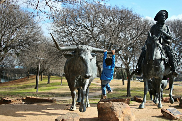 Boy playing on a statue of a longhorn bull in Waco TX