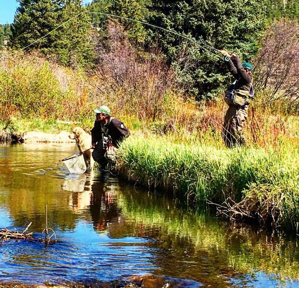 Two people fly-fishing with dog during a dude ranch vacation in Wyoming.