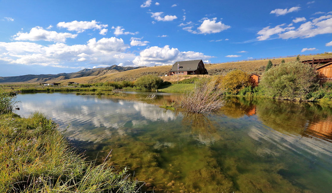 Goosewing Ranch, a Wyoming Dude ranch, landscape shot with pond in foreground.