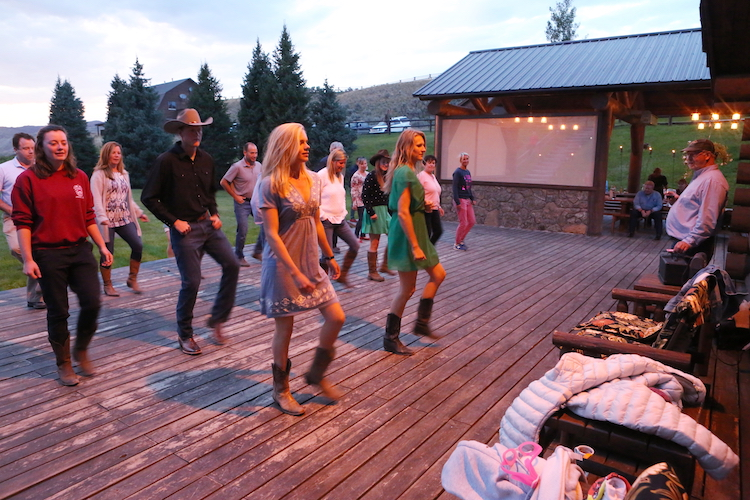 men and women line dancing at dusk at Goosewing Ranch, a dude ranch in wyoming
