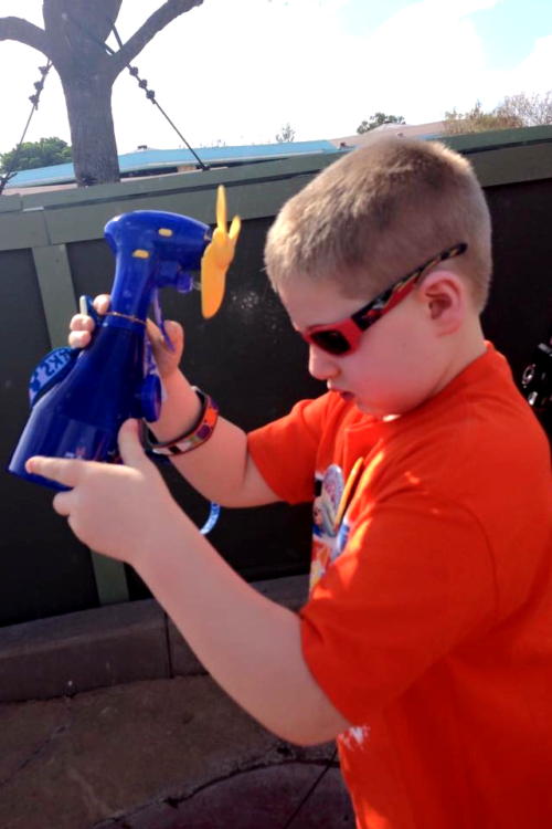 Will uses a mister spray bottle to survive the heat at Disney World.