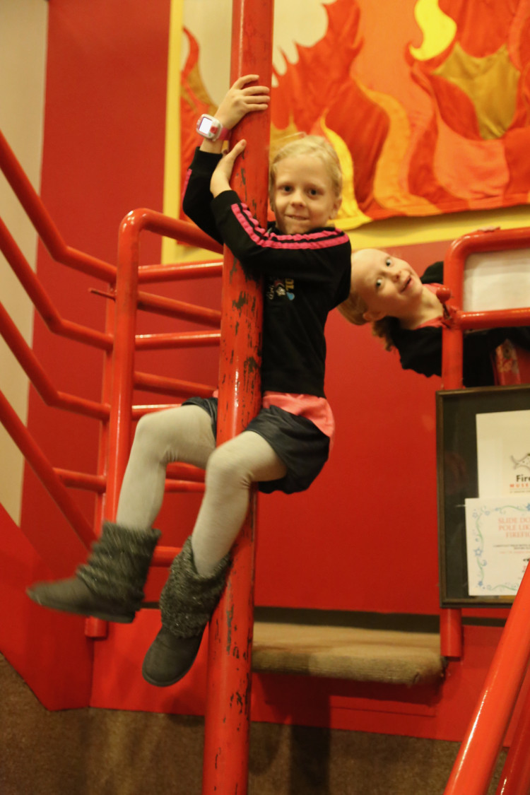 an elementary school girl slides down a fire pole at the Cincinnati Fire Museum - a great staycation idea in Cincinnati