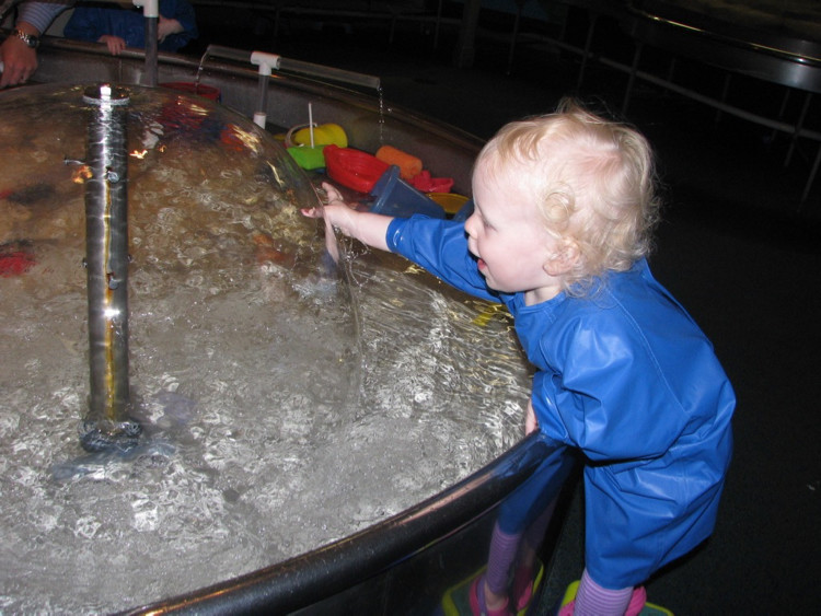 a preschooler plays in a water play area at the Cincinnati Children's Museum in Cincinnati's Union Terminal during a family staycation