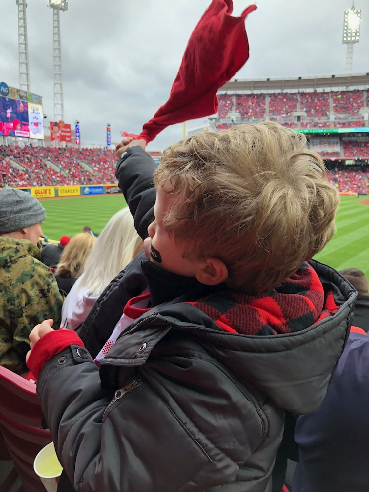 a school-age boy waves a rally towel at Great American Ballpark, during the Cincinnati Reds opening day baseball game