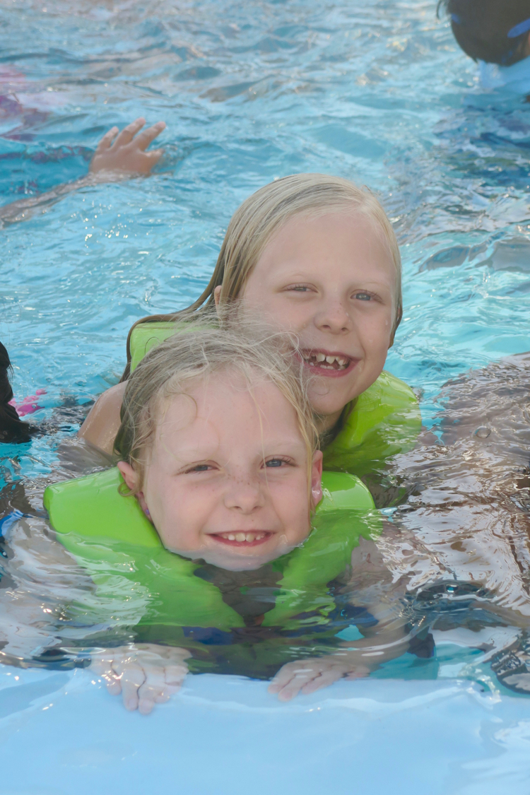 two girls play in the swimming pool on a Disney cruise, in life jackets provided by the ship - not necessary to put on your Disney Cruise Packing List