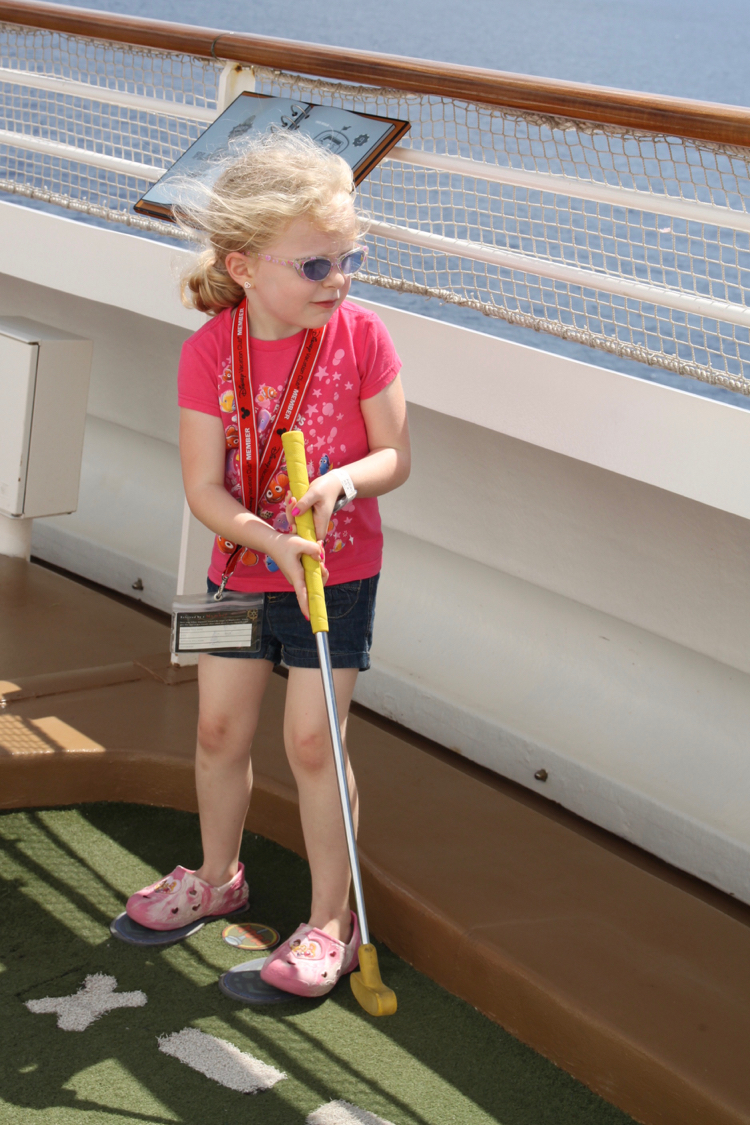 preschool girl playing mini golf on the upper decks of the Disney Fantasy on a Disney Cruise Family trip