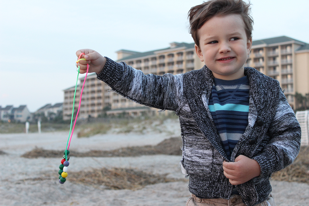 The Fabulously Frugal TravelingMom's son showing off his shark tooth necklace found in Amelia Island.
