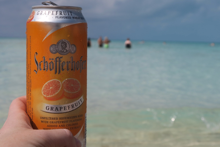 a grapefruit beer in the foreground, with Disney's Castaway Cay Serenity Bay in the background