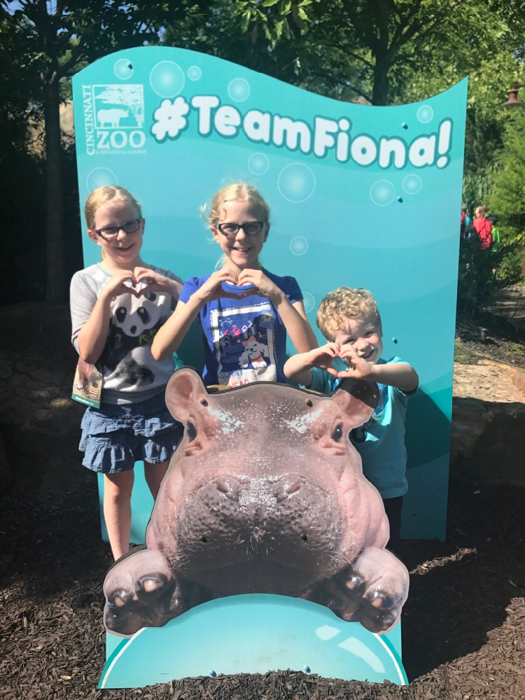 three kids pose with a #TeamFiona sign at the Cincinnati Zoo