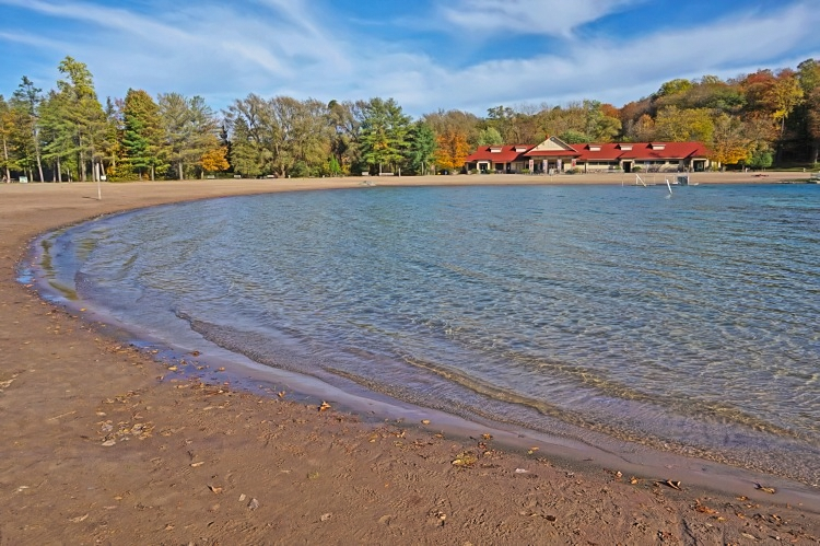 Wide sandy beach at Green Likes State Park, NY invites everyone to play during the warm summer months .