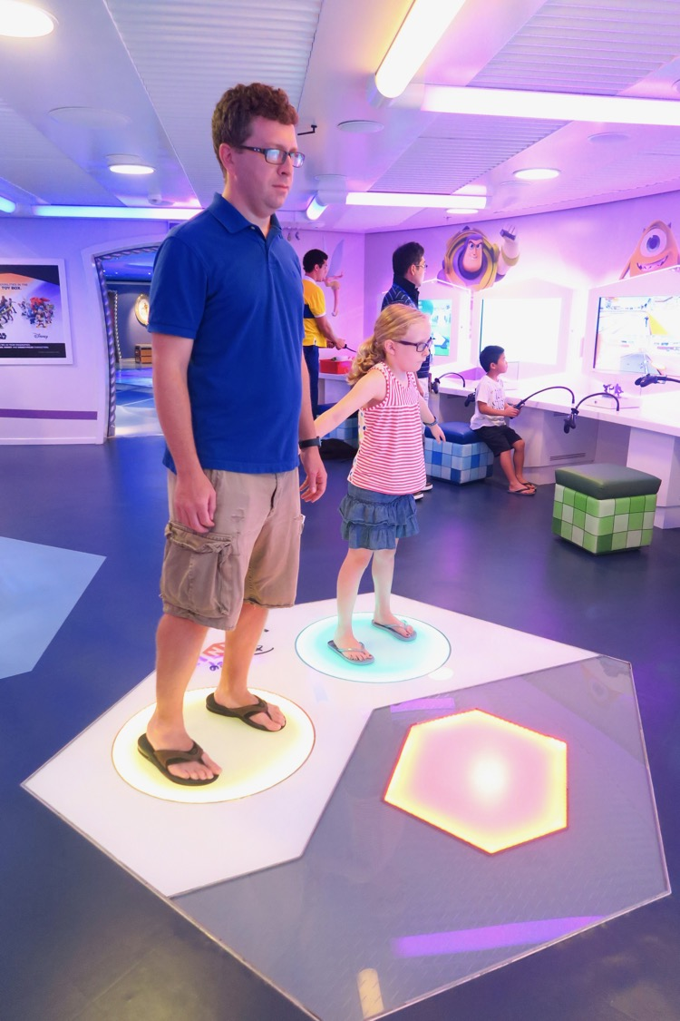a man and daughter play Disney Infinity in the Oceaneer Club on the Disney Dream. Cruising with kids is easier on a ship with plenty for them to do!