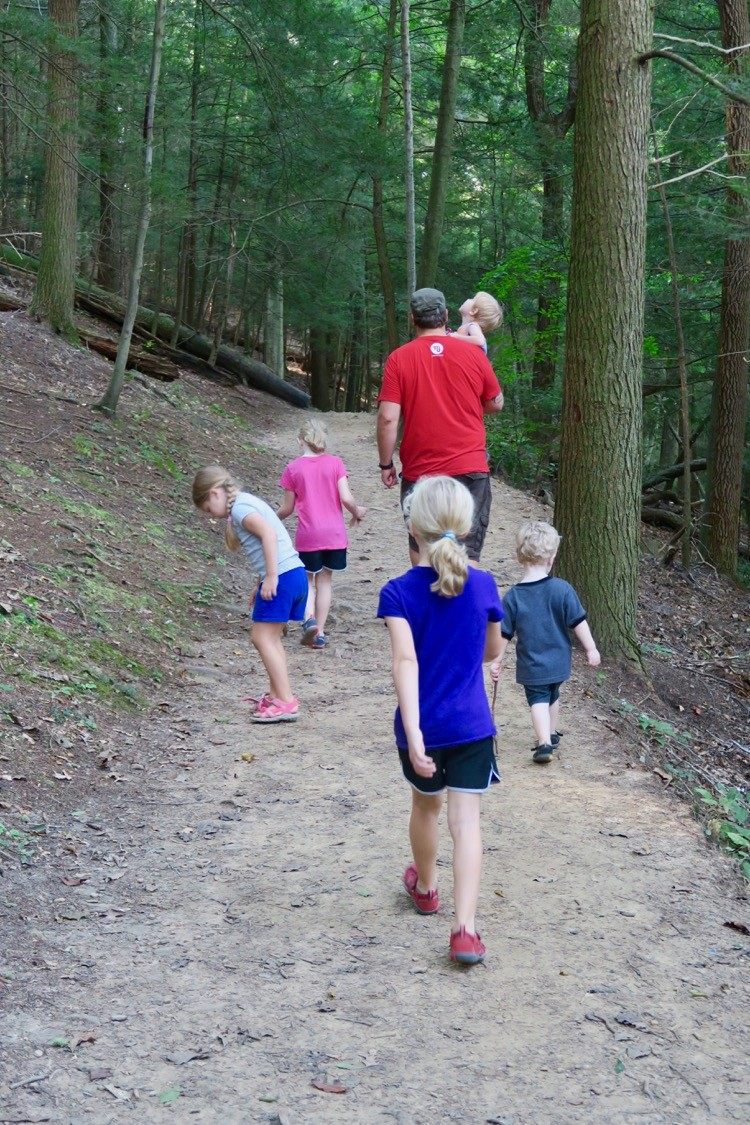 a group of kids hikes behind a man on a trail in Hocking Hills, near Logan, Ohio.