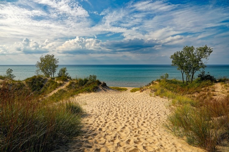 Sand dunes, turquoise water, and a bright blue sky make Indiana Dunes a great stop on a Midwest road trip