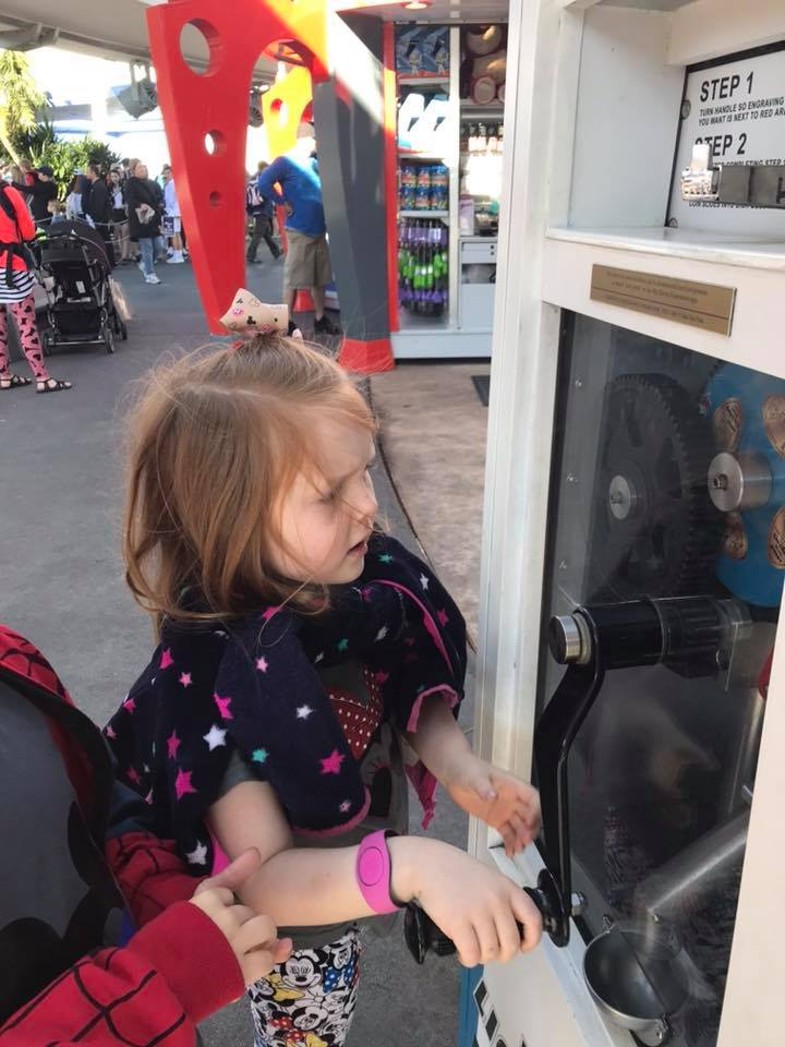 little girl makes a pressed penny at a disney world souvenir machine