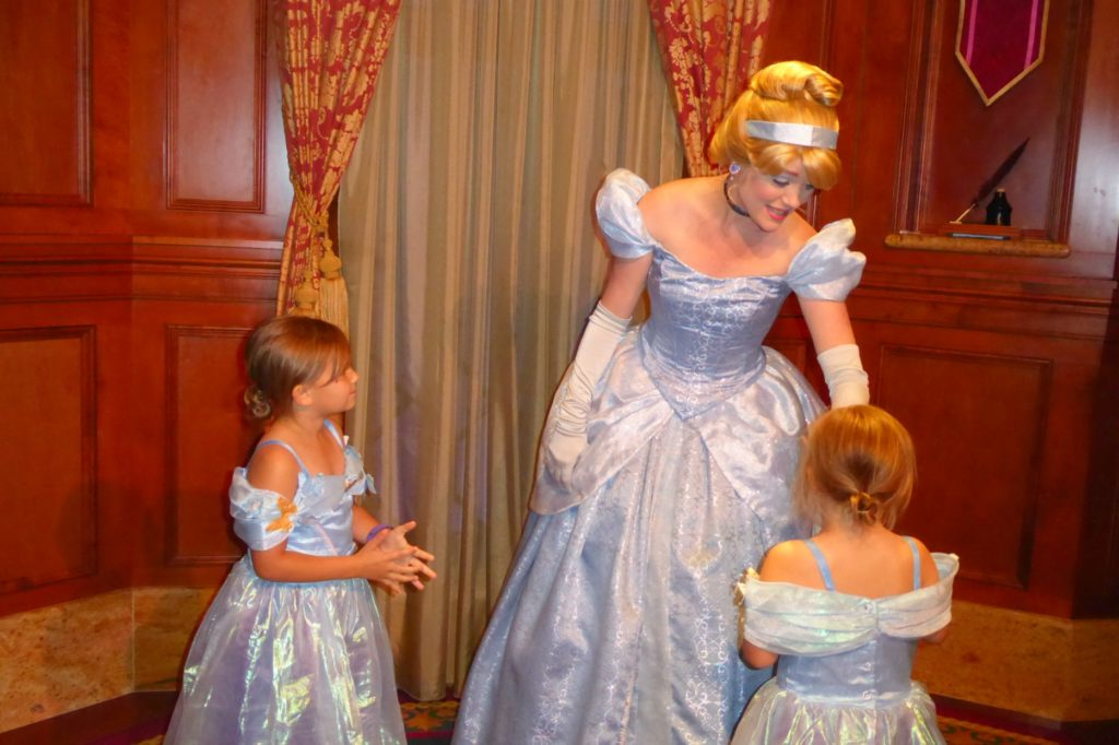 two little girls dressed as cinderella meet cinderella at walt disney world's magic kingdom