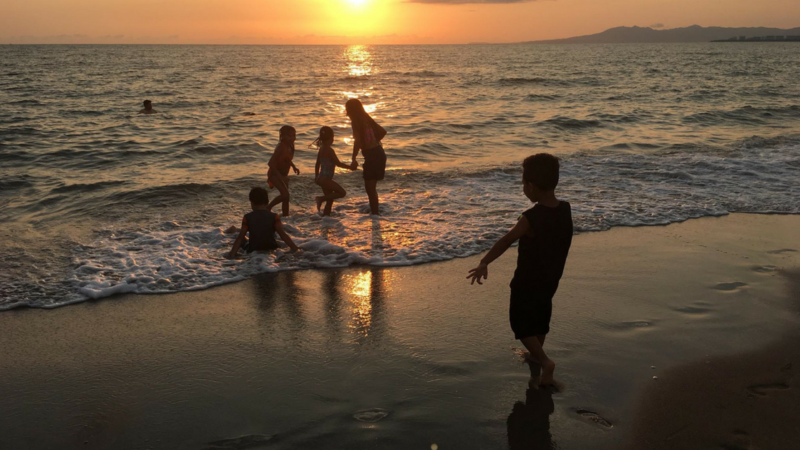 Children play under a beautiful sunset on the beach in Puerto Vallarta, Mexico.