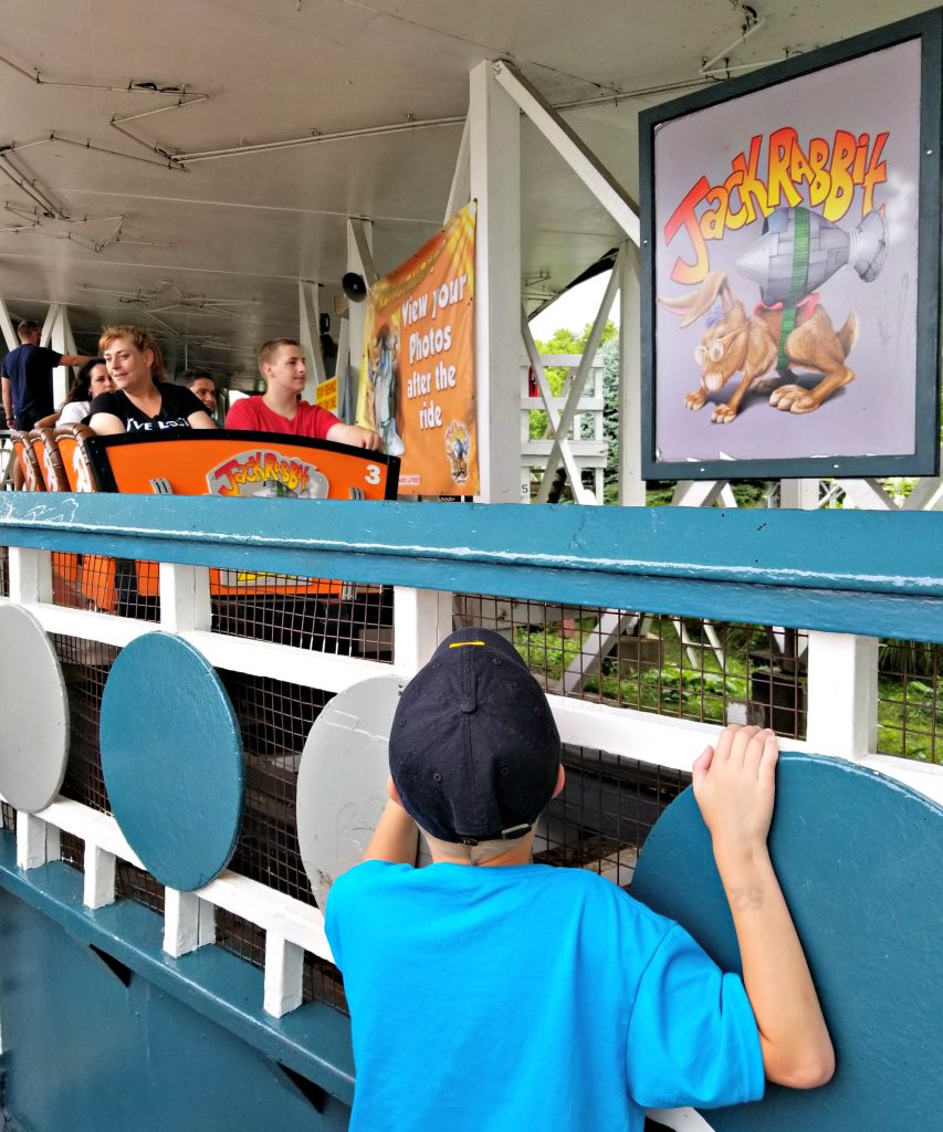 boy watches the wooden roller coaster at Kennywood Amusement Park in Pittsburgh PA